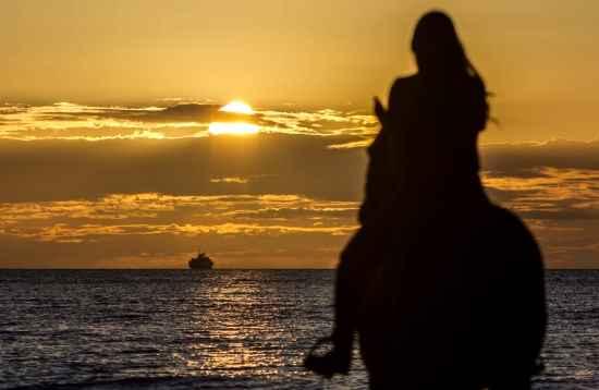 Reiten bei Sonnenuntergang am Meer in El Cotillo